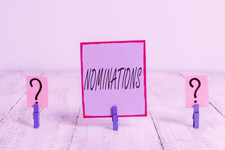 Handwriting text Nominations. Conceptual photo action of nominating or state being nominated for prize Scribbled and crumbling sheet with paper clips placed on the wooden table Stock Photo