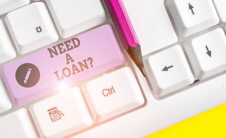 Text sign showing Need A Loan question. Business photo text amount of money that is borrowed often from bank White pc keyboard with empty note paper above white background key copy space