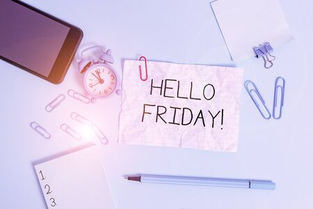 Handwriting text Hello Friday. Conceptual photo used to express happiness from beginning of fresh week Alarm clock clips notepad smartphone rubber band marker colored background