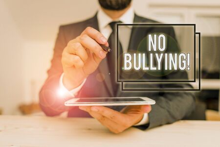 Conceptual hand writing showing No Bullying. Concept meaning stop aggressive behavior among children power imbalance Male human wear formal clothes present use hitech smartphone Stock fotó - 134001973