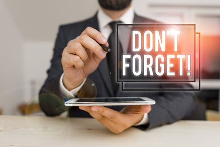 Conceptual hand writing showing Don T Forget. Concept meaning used to remind someone about important fact or detail Male human wear formal clothes present use hitech smartphone