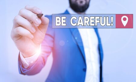 Text sign showing Be Careful. Business photo showcasing making sure of avoiding potential danger mishap or harm Businessman pointing with pen in empty copy space