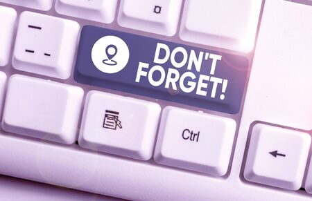 Writing note showing Don T Forget. Business concept for used to remind someone about important fact or detail White pc keyboard with note paper above the white background