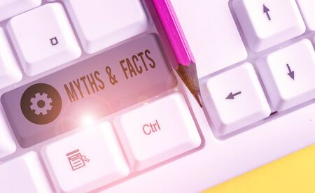 Text sign showing Myths And Facts. Business photo showcasing usually traditional story of ostensibly historical events White pc keyboard with empty note paper above white background key copy space