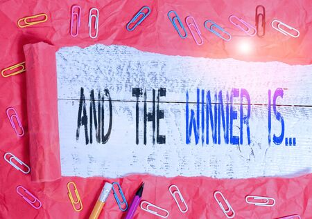 Handwriting text writing And The Winner Is. Conceptual photo announcing a demonstrating or thing that wins something Stationary and torn cardboard placed above a wooden classic table backdrop