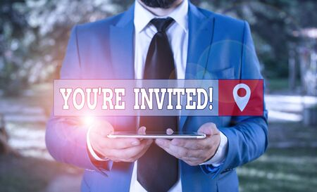 Writing note showing You Re Invited. Business concept for make a polite friendly request to someone go somewhere Businessman in blue suite with a tie holds lap top in hands