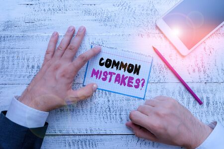 Conceptual hand writing showing Common Mistakes question. Concept meaning repeat act or judgement misguided or wrong Hand hold note paper near writing equipment and smartphone