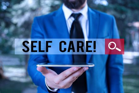 Handwriting text writing Self Care. Conceptual photo practice of taking action to preserve or improve ones own health Businessman in blue suite with a tie holds lap top in hands