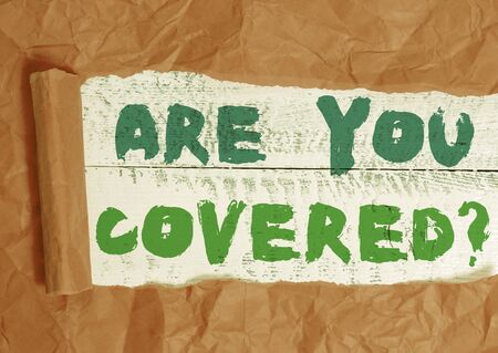 Conceptual hand writing showing Are You Covered Question. Concept meaning asking showing if they had insurance in work or life Cardboard which is torn placed above a wooden classic table Stock fotó