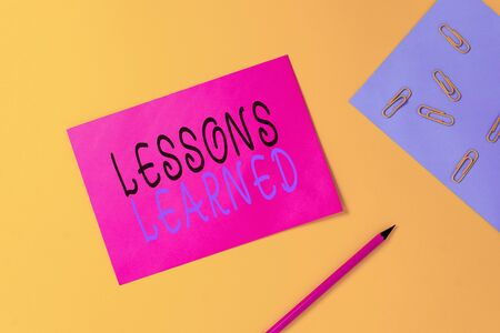 Writing note showing Lessons Learned. Business concept for experiences distilled project that should actively taken Blank paper sheets message pencil clips binder plain colored background