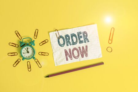 Handwriting text Order Now. Conceptual photo the activity of asking for goods or services from a company Metal alarm clock clips crushed sheet pencil rubber band colored background