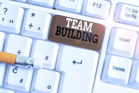 Text sign showing Team Building. Business photo text various types of activities used to enhance social relations White pc keyboard with empty note paper above white background key copy space