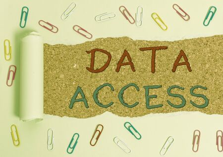 Handwriting text Data Access. Conceptual photo a user s is ability to access data stored within a database Paper clip and torn cardboard placed above a wooden classic table backdrop Stock Photo