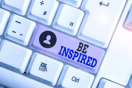 Conceptual hand writing showing Be Inspired. Concept meaning give oneself the desire or enthusiasm to do something well White pc keyboard with note paper above the white background