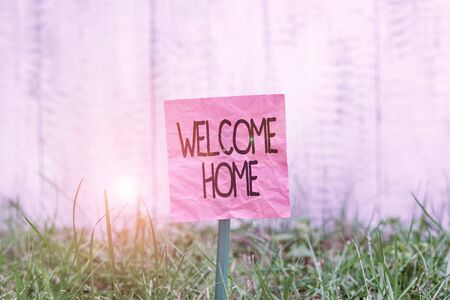 Conceptual hand writing showing Welcome Home. Concept meaning a reception usually celebrate the return home of a demonstrating Plain paper attached to stick and placed in the grassy land Banco de Imagens