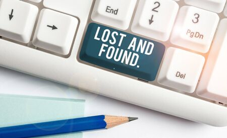 Text sign showing Lost And Found. Business photo showcasing a place where lost items are stored until they reclaimed White pc keyboard with empty note paper above white background key copy space
