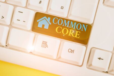 Word writing text Common Core. Business photo showcasing set of academic standards in mathematics and English language White pc keyboard with empty note paper above white background key copy space