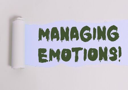 Word writing text Managing Emotions. Business photo showcasing ability be open to feelings and modulate them in oneself Cardboard which is torn in the middle placed above a plain table backdrop
