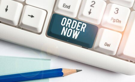 Text sign showing Order Now. Business photo showcasing the activity of asking for goods or services from a company White pc keyboard with empty note paper above white background key copy space