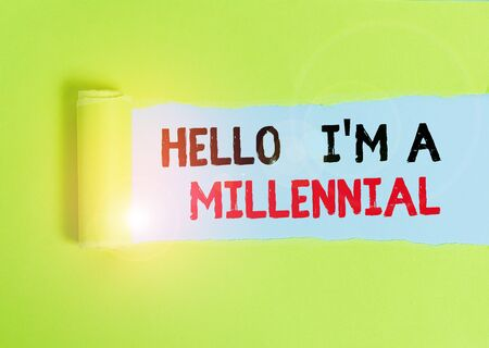 Text sign showing Hello I M A Millennial. Business photo text demonstrating reaching young adulthood in current century Cardboard which is torn in the middle placed above a plain table backdrop Foto de archivo