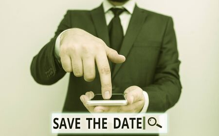 Text sign showing Save The Date question. Business photo text asking someone to remember specific day or time Male human wear formal work suit hold smart hi tech smartphone use one hand Stok Fotoğraf - 133423316