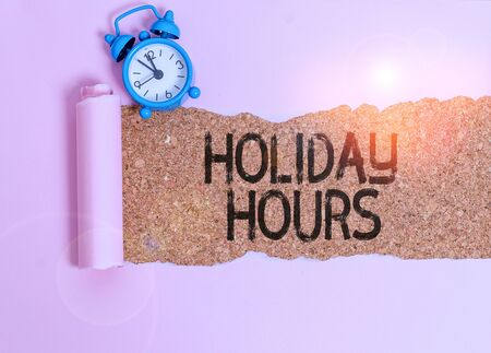 Text sign showing Holiday Hours. Business photo showcasing employee receives twice their normal pay for all hours Alarm clock and torn cardboard placed above a wooden classic table backdrop