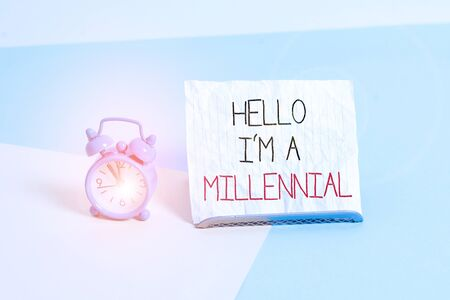 Conceptual hand writing showing Hello I M A Millennial. Concept meaning demonstrating reaching young adulthood in current century Alarm clock beside a Paper sheet placed on pastel backdrop
