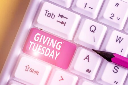 Writing note showing Giving Tuesday. Business concept for international day of charitable giving Hashtag activism White pc keyboard with note paper above the white background Foto de archivo