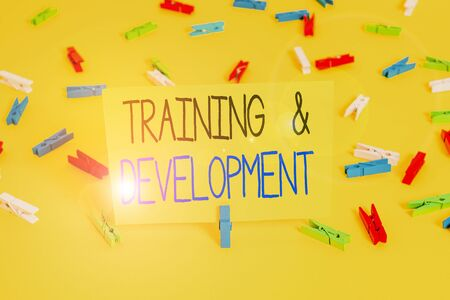 Text sign showing Training And Development. Business photo text learn specific knowledge to improve perforanalysisce Colored clothespin papers empty reminder yellow floor background office