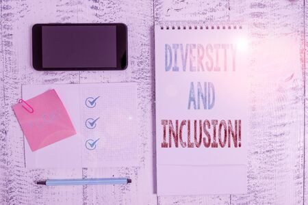 Writing note showing Diversity And Inclusion. Business concept for range huanalysis difference includes race ethnicity gender Square spiral notebook marker smartphone sticky note on wood background