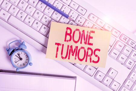 Conceptual hand writing showing Bone Tumors. Concept meaning can be either benign or malignant growths found in the bone Flat lay above empty note paper on pc keyboard pencils and clock Stockfoto