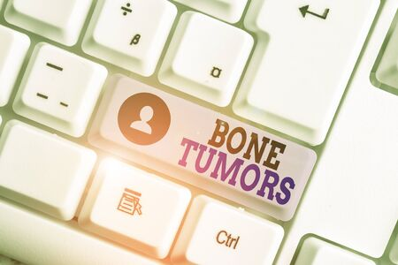 Conceptual hand writing showing Bone Tumors. Concept meaning can be either benign or malignant growths found in the bone White pc keyboard with note paper above the white background