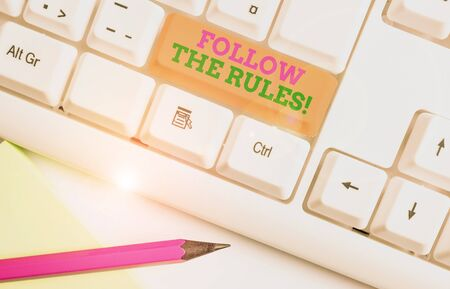 Text sign showing Follow The Rules. Business photo showcasing go with regulations governing conduct or procedure White pc keyboard with empty note paper above white background key copy space