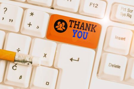 Text sign showing Thank You. Business photo showcasing a polite expression used when acknowledging a gift or service White pc keyboard with empty note paper above white background key copy space