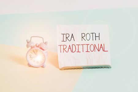 Conceptual hand writing showing Ira Roth Traditional. Concept meaning are tax deductible on both state and federal Alarm clock beside a Paper sheet placed on pastel backdrop