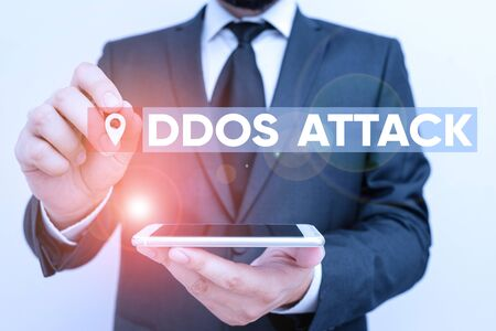 Conceptual hand writing showing Ddos Attack. Concept meaning perpetrator seeks to make a network resource unavailable to user Male human wear formal work suit hold smartphone using hand