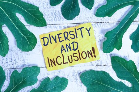 Text sign showing Diversity And Inclusion. Business photo text range huanalysis difference includes race ethnicity gender Leaves surrounding notepaper above a classic wooden table as the background