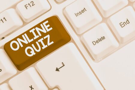 Writing note showing Online Quiz. Business concept for game or a mind sport that are published on the Internet White pc keyboard with note paper above the white background Stockfoto