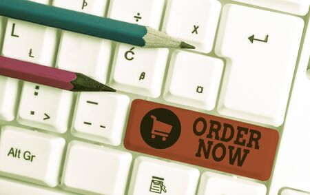 Writing note showing Order Now. Business concept for the activity of asking for goods or services from a company White pc keyboard with note paper above the white background Reklamní fotografie