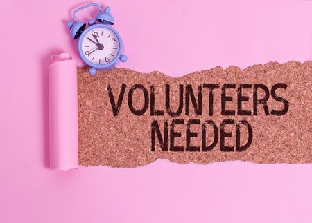 Text sign showing Volunteers Needed. Business photo showcasing need work or help for organization without being paid Alarm clock and torn cardboard placed above a wooden classic table backdrop Stockfoto
