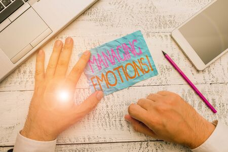 Writing note showing Managing Emotions. Business concept for ability be open to feelings and modulate them in oneself Hand hold note paper near writing equipment and smartphone