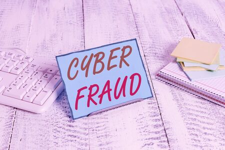 Word writing text Cyber Fraud. Business photo showcasing any crime that is committed with the use of a computer Notepaper stand on buffer wire in between computer keyboard and math sheets Stock Photo