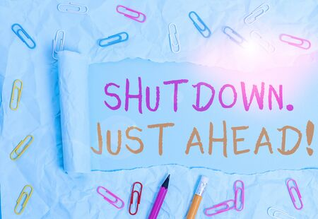 Conceptual hand writing showing Shutdown Just Ahead. Concept meaning closing factory business either short time or forever Stationary and torn cardboard on a plain pastel table backdrop 스톡 콘텐츠