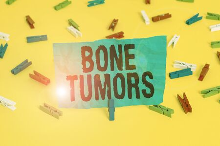 Conceptual hand writing showing Bone Tumors. Concept meaning can be either benign or malignant growths found in the bone Colored clothespin papers empty reminder yellow floor office Stockfoto