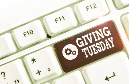 Handwriting text Giving Tuesday. Conceptual photo international day of charitable giving Hashtag activism White pc keyboard with empty note paper above white background key copy space