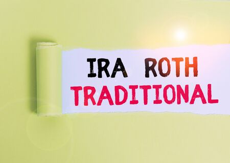 Text sign showing Ira Roth Traditional. Business photo text are tax deductible on both state and federal Cardboard which is torn in the middle placed above a plain table backdrop Stock Photo