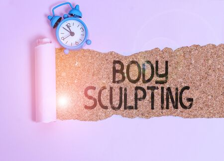 Text sign showing Body Sculpting. Business photo showcasing activity of increasing the body s is visible muscle tone Alarm clock and torn cardboard placed above a wooden classic table backdrop