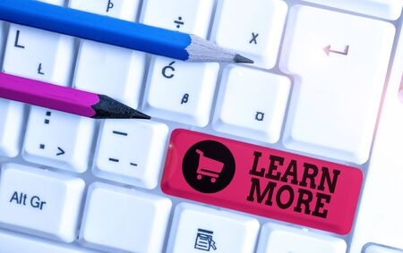Writing note showing Learn More. Business concept for knowledge or skill acquired by instruction Considerable learning White pc keyboard with note paper above the white background