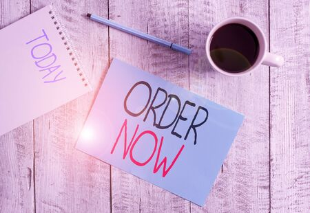 Writing note showing Order Now. Business concept for the activity of asking for goods or services from a company Stationary placed next to a cup of black coffee above the wooden table Archivio Fotografico - 133483908