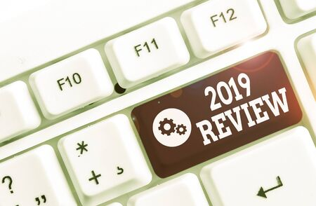 Handwriting text 2019 Review. Conceptual photo New trends and prospects in tourism or services for 2019 White pc keyboard with empty note paper above white background key copy space